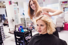 Hairdresser making a new haircut to her handsome client Royalty Free Stock Image