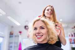 Hairdresser making a new haircut to her handsome client Stock Photography