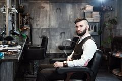 Hairdresser man shaves a client with a beard in a barbershop. The hairdresser man in glasses cuts and shaves a beard to the young handsome man to the client in a stock image