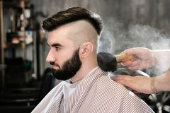 Hairdresser man shaves a client with a beard in a barbershop Royalty Free Stock Image