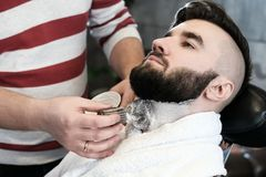 Hairdresser man shaves a client with a beard in a barbershop Royalty Free Stock Photography