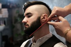Hairdresser man shaves a client with a beard in a barbershop Stock Image