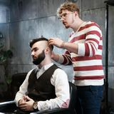 Hairdresser man shaves a client with a beard in a barbershop Royalty Free Stock Photos