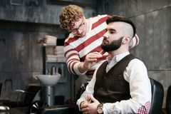 Hairdresser man shaves a client with a beard in a barbershop Stock Images