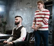 Hairdresser man shaves a client with a beard in a barbershop Stock Photos