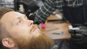 Hairdresser for men. Barbershop. Caring for the beard. Barber with hair clipper works on hairstyle for bearded guy stock footage