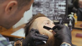 Hairdresser for men. Barbershop. Caring for the beard. Barber with hair clipper works on hairstyle for bearded guy. Barbershop background. Hipster lifestyle stock video footage