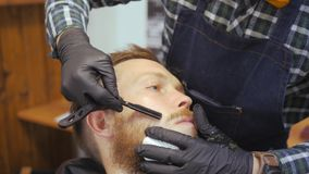 Hairdresser for men. Barbershop. Caring for the beard. Barber with hair clipper works on hairstyle for bearded guy stock video footage