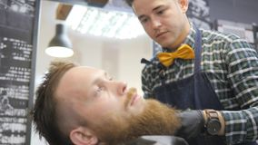 Hairdresser for men. Barbershop. Caring for the beard. Barber with hair clipper works on hairstyle for bearded guy stock video