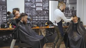 Hairdresser for men. Barbershop. Caring for the beard. Barber with hair clipper works on hairstyle for bearded guy. Barbershop background. Hipster lifestyle stock video