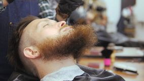 Hairdresser for men. Barbershop. Caring for the beard. A hairdresser with a haircut works over the beard and mustache of stock footage