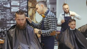 Hairdresser for men. Barbershop. Hair care for a young guy. Hairdresser with a haircut works for a hairstyle for a stock footage