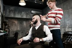 Hairdresser man shaves a client with a beard in a barbershop Royalty Free Stock Photo