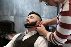 Hairdresser man shaves a client with a beard in a barbershop Royalty Free Stock Images