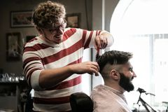 Hairdresser man shaves a client with a beard in a barbershop Stock Photo