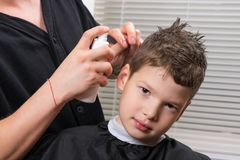 The hairdresser moistens the boys hair with a sprayer to do the haircut. The hairdresser moistens the boy`s hair with a sprayer to do the haircut royalty free stock images