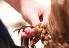 Hairdresser plaiting hair little girl child in hairdressing beauty salon Royalty Free Stock Image