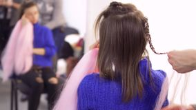 Hairdresser plaits braids with pink artificial strands with to a young woman. Hairdresser plaits the braids with pink artificial hair to a young woman for her stock video