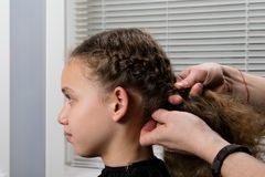 The hairdresser plaits a pigtail to a child, with curly hair Stock Photography