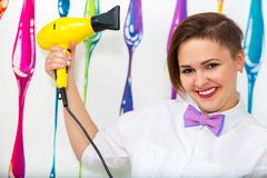 The hairdresser. Portrait of a beautiful smiling woman with a hair dryer in hands Stock Photo