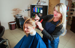 Hairdresser prepares for work with young woman. Stock Images