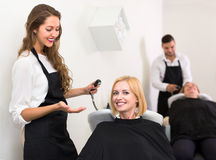Hairdresser preparing to wash client's head Royalty Free Stock Images