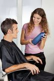 Hairdresser Presenting Shampoo Bottle To The Royalty Free Stock Image