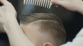 Hairdresser puts hair to his little client. The boy has a new haircut. Baby haircut in barbershop
