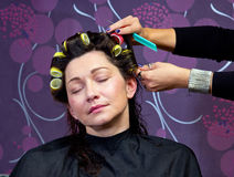 Hairdresser putting rollers in woman hair Royalty Free Stock Images