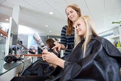 Hairdresser Referring Hairstyle From Magazine Stock Photos