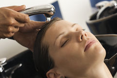 Hairdresser rinsing woman's hair in salon, customer with eyes closed, close-up royalty free stock photography