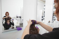 Hairdresser Rolling Up Curler For Client Stock Photos