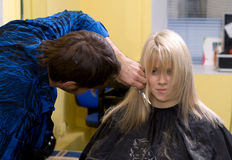 Hairdresser's. Barber makes a hair-dress to the young blond Royalty Free Stock Photo