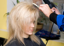 Hairdresser's. Barber makes a hair-dress to the young blond Royalty Free Stock Photography