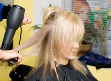 Hairdresser's. Barber makes a hair-dress to the young blonde Royalty Free Stock Photography