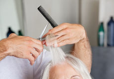 Hairdresser's Hand Cutting Hair In Parlor Stock Image