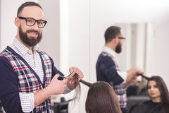 Hairdresser's. Male hairdresser making a haircut for a beautiful brunette girl in professional hairdressing salon and looking at camera Royalty Free Stock Image