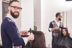 Hairdresser's. Male hairdresser making a haircut for a beautiful brunette girl in professional hairdressing salon and looking at camera Stock Images