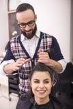 Hairdresser's. Professional hairdresser making hair for a brunette girl in hairdresser salon Stock Images