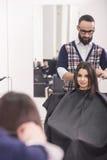Hairdresser's. Professional hairdresser making hair for a brunette girl in hairdresser salon Stock Image