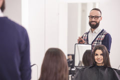 Hairdresser's. Professional hairdresser showing for beautiful client her new hairdo in hairdressing salon Stock Photography