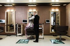 Hairdresser`s salon with one client being served, black chairs and huge clean mirrors stock photography