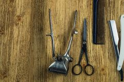 Hairdresser`s tools. Vintage hairdressing tools on a rough wooden surface free space on the left Royalty Free Stock Photos