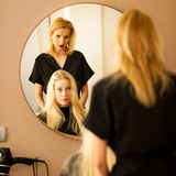 In hairdresser salon - hair stylist consulting a customer before Royalty Free Stock Image