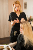 In hairdresser salon - hair stylist consulting a customer before Royalty Free Stock Images