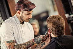 Hairdresser with scissors cut the beard close up Royalty Free Stock Photography