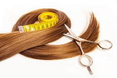 Hairdresser scissors on hair with measuring tape Royalty Free Stock Image
