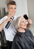Hairdresser Setting Up Customer's Hair. Portrait of male hairdresser with hairspray and hairbrush setting up female customer's hair at beauty salon stock images