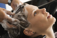 Hairdresser shampooing woman's hair in salon, close-up, profile Royalty Free Stock Photo