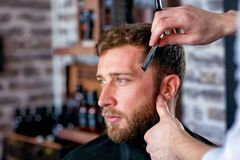 Hairdresser shaves man`s beard with a blade Stock Photo
